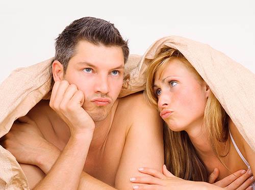 Мужчина и женщина в постели думают применить крем для продления полового акта