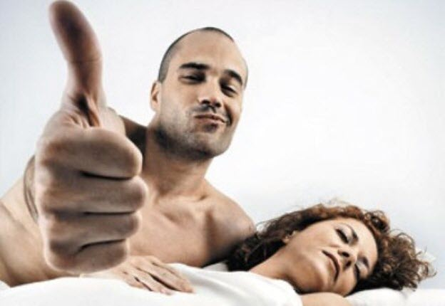 Мужчина с пальцем вверх с женщиной в кровати